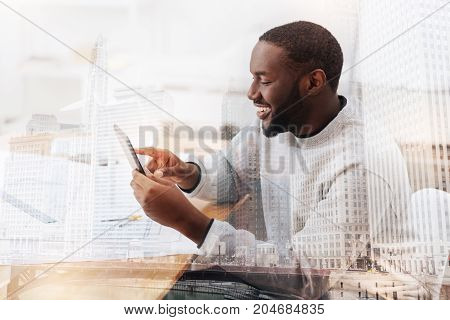 Perfect mood. Young excited African American using a tablet while smiling and touching the screen with a finger