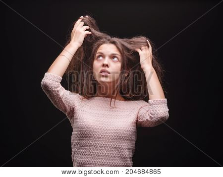 Portrait of a young casual woman with health, and hair problems on a black background. Stressed female pulling tangled, frizzy, sick, problematic hair. Healthcare and treatment of stress concept.