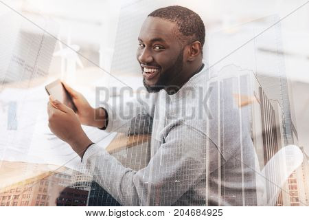 Being curious. Close up of cheerful handsome African American sitting at the table while holding digital tablet and looking at you