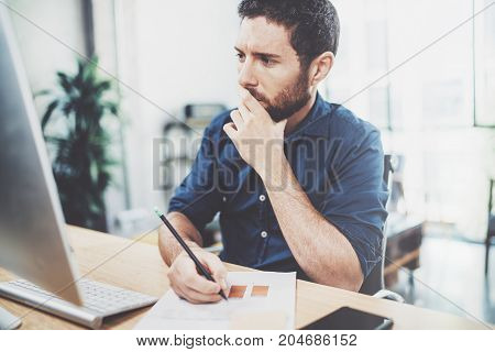 Young elegant banking finance analyst working at sunny office on laptop while sitting at wooden table.Businessman analyze stock reports.Blurred background, horizontal