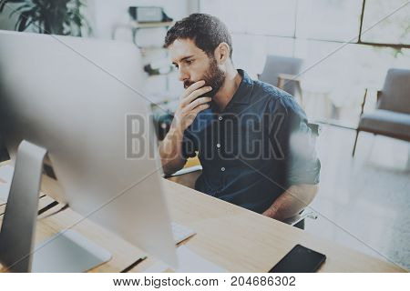 Young pensive businessman working at sunny office while sitting at the wooden table.Man analyze document on desktop computer.Blurred background