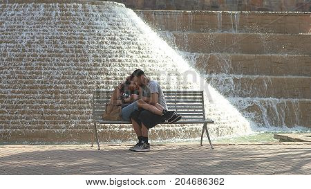 San Antonio, Texas - February 20, 2011: Romantic couple sitting on the bench near the fountain on Riverwalk in San Antonio, Texas.