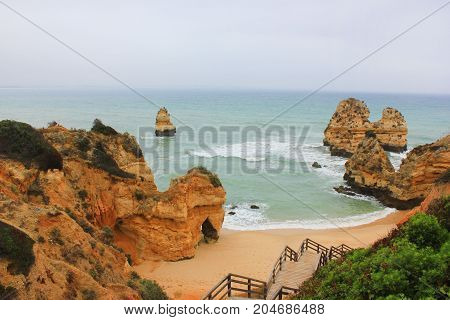 Praia do Camilo Beach in Lagos, Algarve Coast, Portugal. Famous travel destination for tourists in Europe with beautiful landscape views. Summer empty nature scene with no people around and copyspace