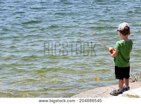 Austin, Texas - May 6, 2017: Little boy fishing in the reservoir near Austin, Texas.