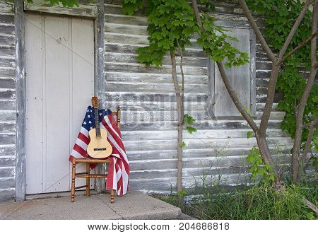 guitar and American flag on wooden chair by rustic wooden house door