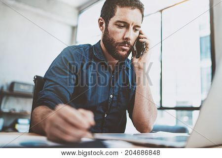 Young businessman using smartphone at office and making notes.Blurred background.Horizontal