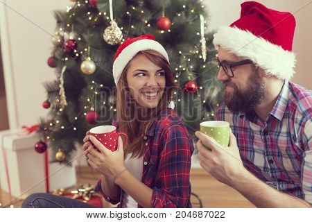 Beautiful young couple in love sitting on a living room floor next to a nicely decorated Christmas tree and drinking coffee. Focus on the girl