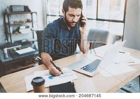 Elegant businessman working at sunny work place on laptop while sitting at the wooden table.Man using smartphone and analyze document on computer notebook.Blurred background.Horizontal