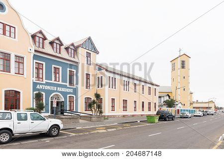 SWAKOPMUND NAMIBIA - JUNE 30 2017: A street scene with historic buildings and the Holy Rosary Roman Catholic Church in Swakopmund in the Namib Desert on the Atlantic Coast of Namibia
