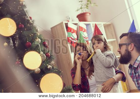Beautiful young family sitting next to a nicely decorated Christmas tree wearing Santa's hats and blowing party whistles. Focus on the baby girl