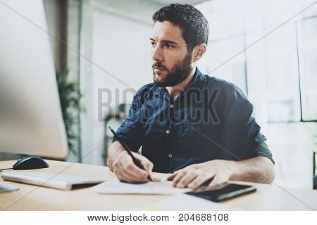 Young handsome man working at sunny office on desk top computer while sitting at wooden table.Businessman analyze stock reports display.Blurred background, horizontal