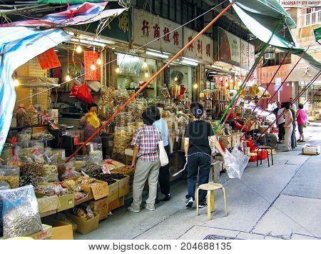 Sheung Wan, Hong Kong - March 25, 2003: Customers are standing in front of traditional shops for food in the Sheung Wan district on Hong Kong Island and buy goods.
