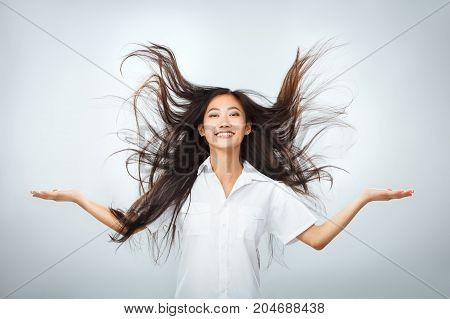 Happy Young Asian Woman With Beautiful Flying Long Hair