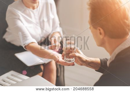 It is for you. Nice professional female psychologist sitting opposite her patient and holding a glass of water while giving it to him