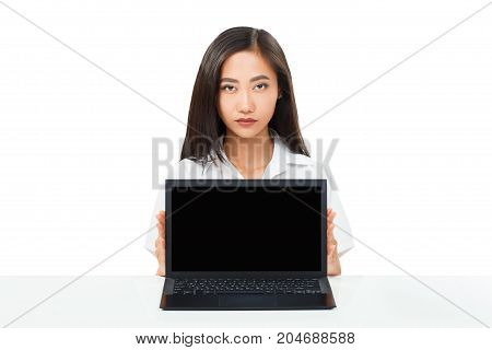 Serious Asian Woman Sitting With Laptop With Black Blank Screen