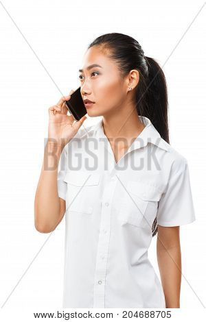 Asian Young Serious Woman Speaking By Mobile Phone Isolated