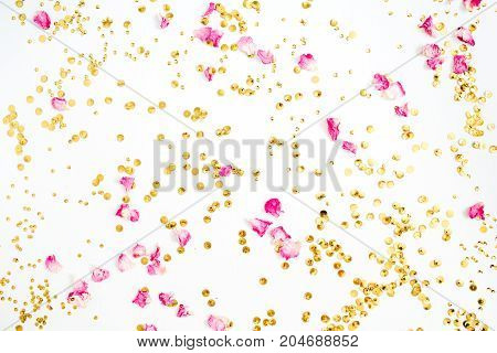 Colorful pattern made of pink rose petals and golden confetti on white background. Flat lay top view.