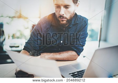 Businessman working at office with paper document. Horizontal.Blurred background