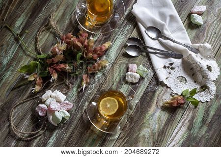 Tea with lemon and slices of shaker-lokum on a wooden table close-up