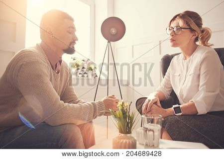 Working with patients. Nice serious good looking therapist sitting in the armchair and listening to her patient while having a psychological session with him