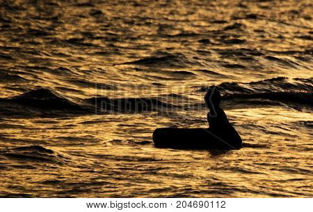 silhouette of kid on beach and in sea in evening before sunset in holiday