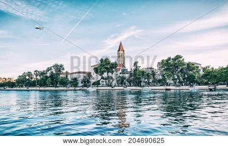 Old town Trogir with Cathedral of St. Lawrence clear water at Adriatic sea and an airplane flies to the nearby Split town. Travel destination. Beauty photo filter.