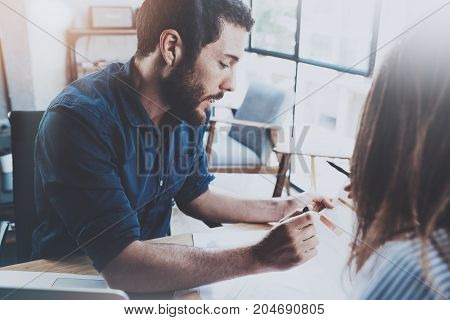 Business partnership concept.Hispanic young businessman working with business woman at sunny office.Blurred background. Horizontal.Flares