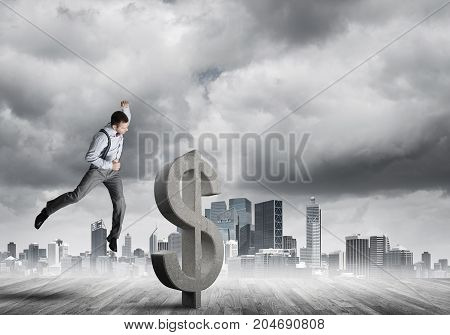 Young furious businessman going to crash with fist stone dollar symbol