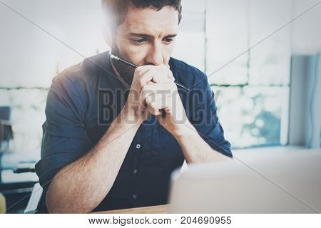Man working at the wooden table at modern loft office.Man sitting in chair and using contemporary laptop.Blurred background.Horizontal.