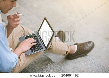 Remote work. Modern technology for men. Social communication. Unrecognizable businessman with bad habits, laptop with empty white screen mockup