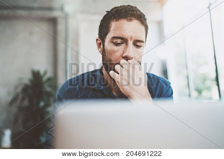 Young Businessman working at modern loft office.Pensive Man sitting and using contemporary laptop.Blurred background.Horizontal.