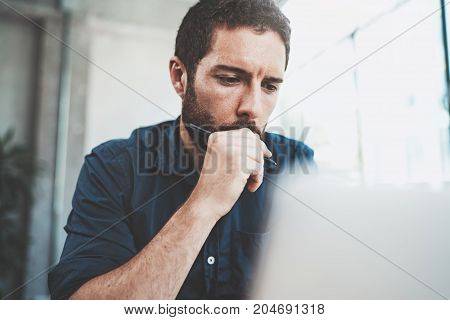 Pensive man using contemporary laptop at office.Blurred background.Horizontal.