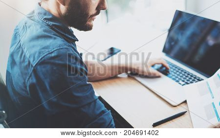 Young pensive man working at sunny office on laptop while sitting at wooden table.Businessman reports on notebook computer.Blurred background, horizontal.Cropped
