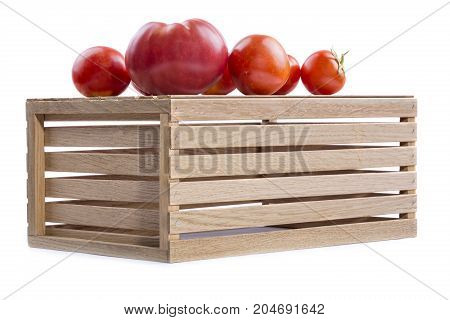Ripe tomatoes on a wooden box on a white background.