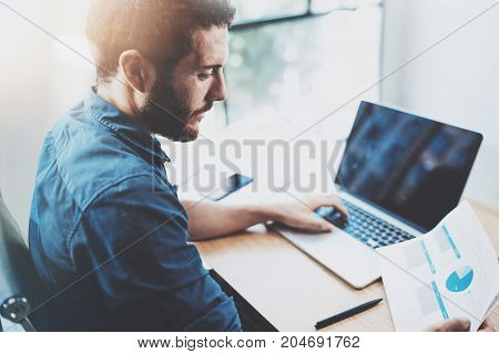 Young bearded man working at sunny loft office on laptop.Businessman analyze paper documents reports in his hand.Blurred background, horizontal