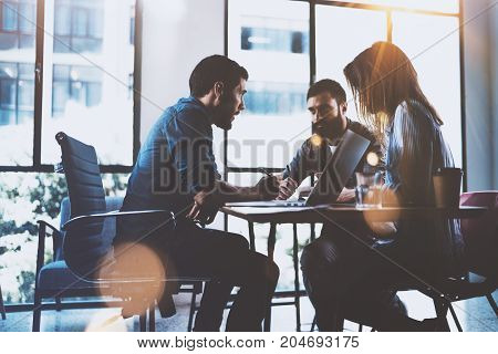Teamwork brainstorming process.Young man working together with partners in modern office loft.Business startup concept.Blurred background.Flares
