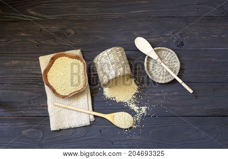 Raw millet in a bamboo box and a bowl on a wooden table close-up