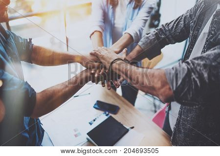Teamwork concept.Group of three coworkers join hand together during their meeting. Horizontal.Blurred background
