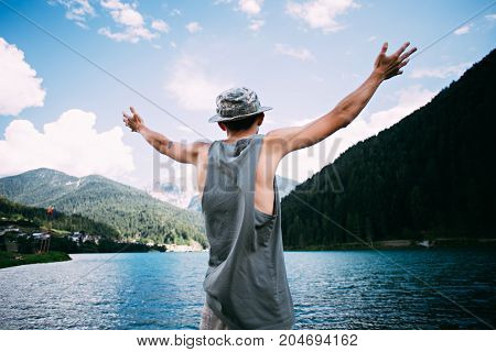 Man in tank top and panama tourist hat raises his hands in awe of beautiful natural wonders forest dolomiti mountains and pristine lake blue skies with clouds