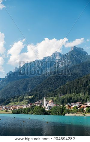 View over beautiful pristine italian village lost high in mountains with tremendous huge rock range over old town blue skies with white clouds over dolomites