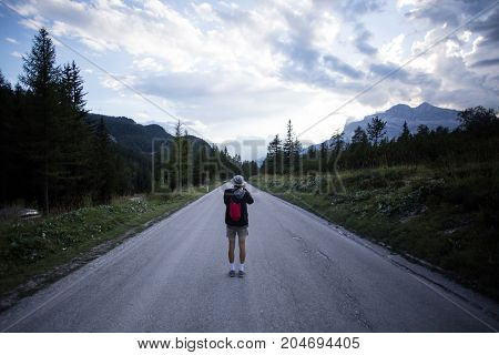 Solo millennial nomad photographer influencer path finder walks on empty road high in mountains during beautiful sunset makes photo of skies and landscape