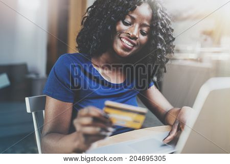 Happy young african american woman shopping online through laptop using credit card at home. Horizontal, blurred background.Cropped