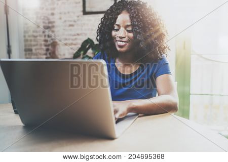 Smiling african american woman using laptop while sitting at wooden table in the living room.Horizontal, blurred background