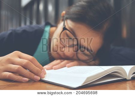 Tired Asian woman sleeping with her book on wooden table.