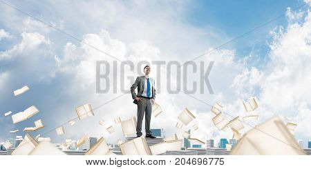 Confident businessman in suit standing on pile of documents among flying books with cloudly sky on background. Mixed media.