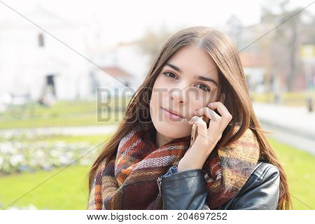 Close up of a young beautiful woman talking on the phone. Outdoors.