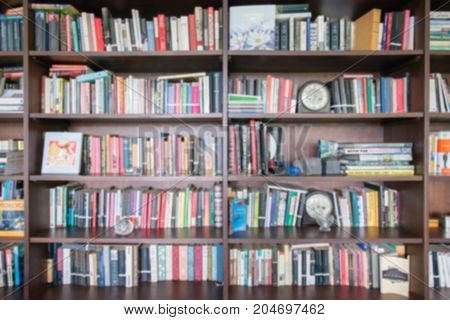 Abstract blur and defocused bookshelf in library interior for background.vintage bookshelf with many book for education in library