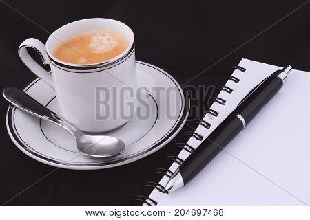 A Cup Of Coffee With A Notepad.