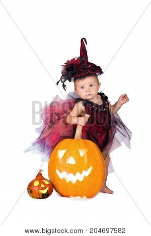 Little witch girl child laughing among pumpkins and candles on a white background