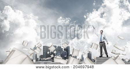 Businessman keeping hand with book up while standing among flying books with cloudly sky on background. Mixed media.